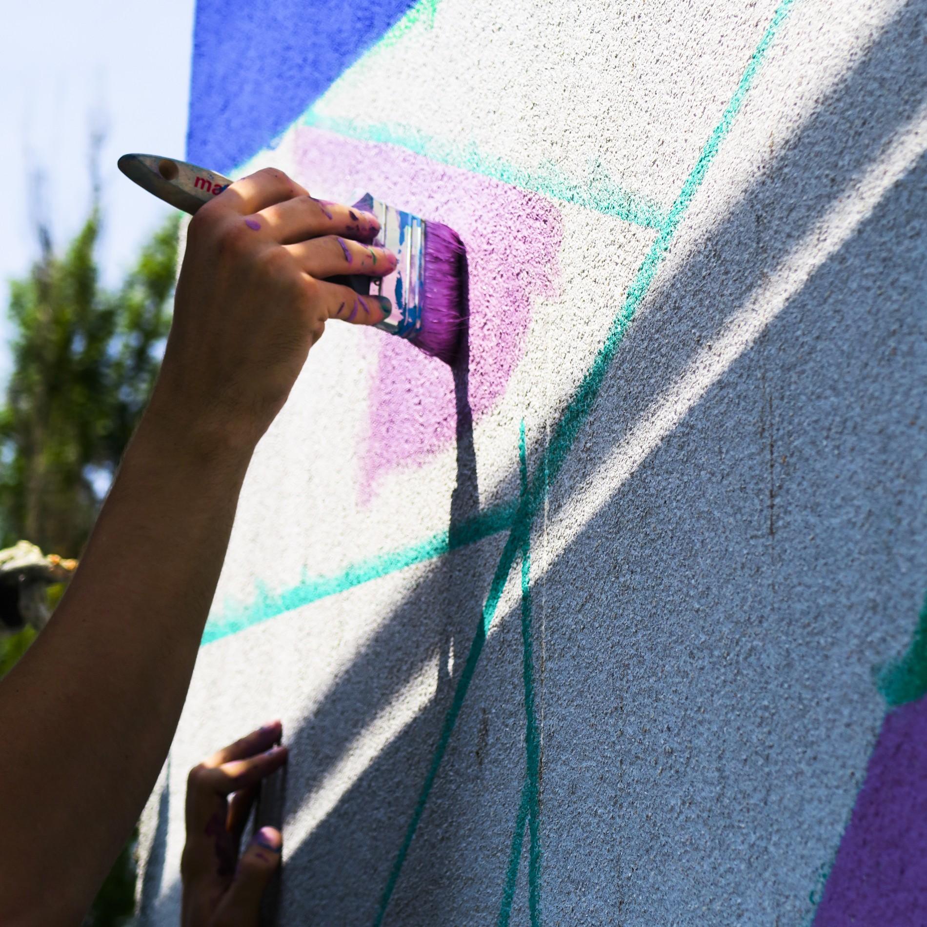 """Dariusz Milczarek w trakcie malowania muralu """"kompozycja kubihutyczna 1"""""""