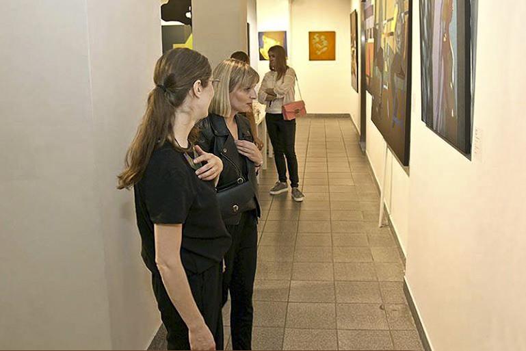 """Kobiety oglądają obraz Dariusza Milczarka w trakcie wernisażu wystawy """"Stany Przejściowe"""""""