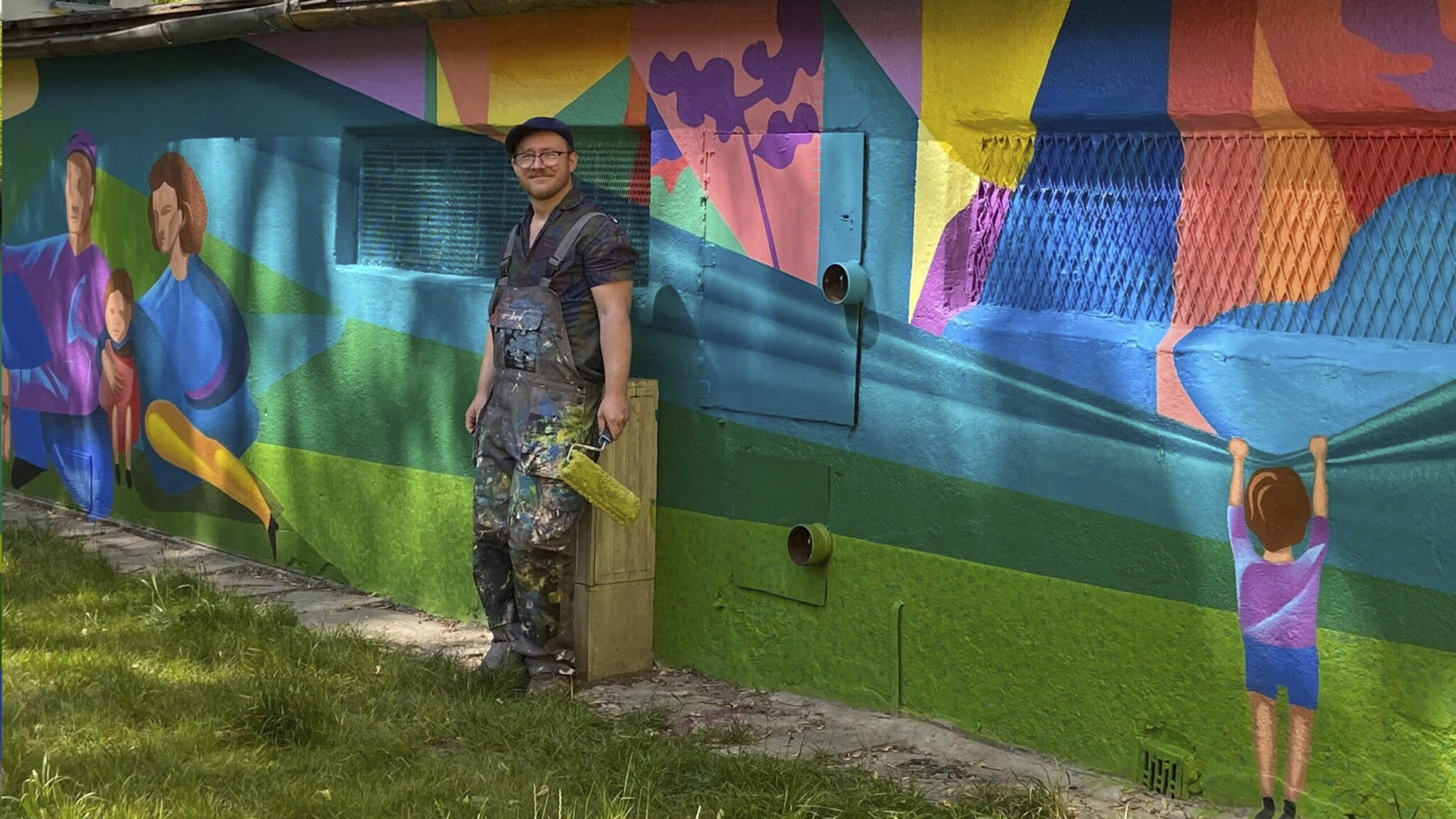 """Dariusz Milczarek na tle muralu """"Przeszłość – współczesność – przyszłość Nowej Huty"""""""