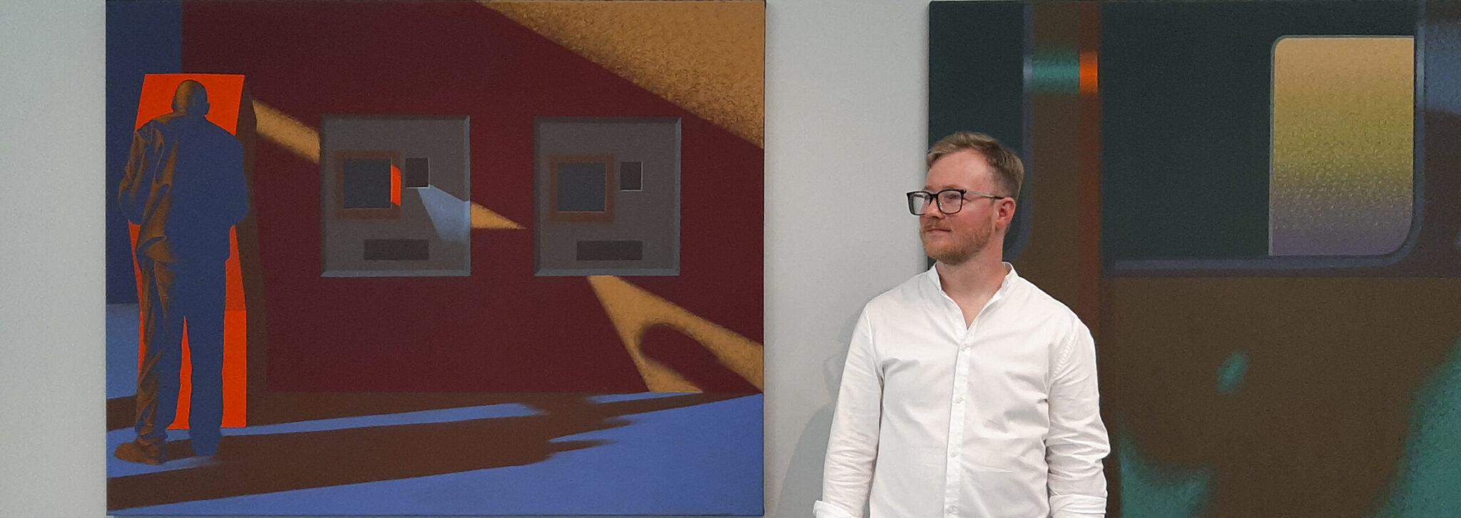 Dariusz Milczarek na tle obrazów na wystawie pokonkursowej w Galerii Miejskiej BWA w Bydgoszczy