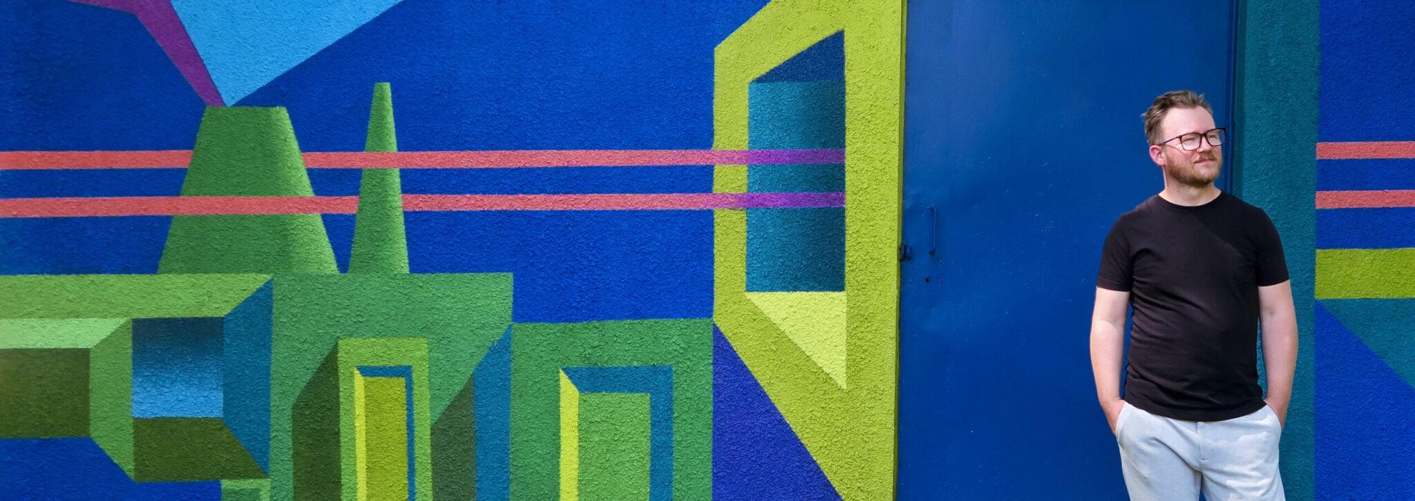 """Dariusz Milczarek na tle muralu """"Tauron-nowa energia"""""""