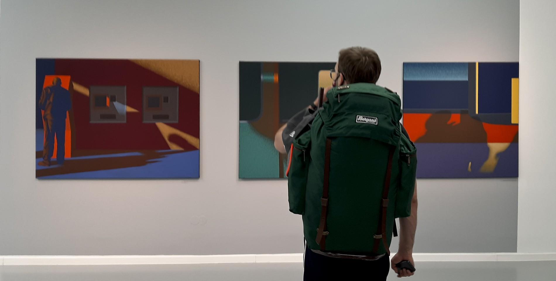 Mężczyzna ogląda obrazy Dariusza Milczarka na wystawie pokonkursowej w Galerii Miejskiej BWA w Bydgoszczy